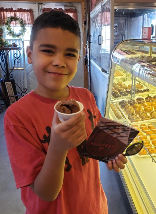 Boy with chocolate passport and ice cream