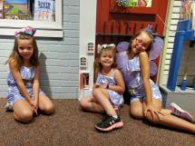 three girls in front of a fairy door